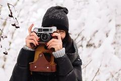 A menina de sorriso fotografou em uma câmera no inverno Fotos de Stock Royalty Free