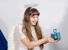 A menina de sorriso guarda um presente nas palmas Fotografia de Stock