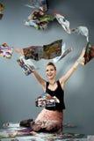 A menina de sorriso joga acima jornais Fotos de Stock
