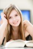 A menina de sorriso lê o livro grosso Foto de Stock Royalty Free