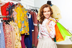 A menina de sorriso leva sacos de compras na alameda Imagens de Stock Royalty Free