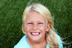 Menina de sorriso loura bonita que senta-se na grama em um dia de verão Imagem de Stock Royalty Free