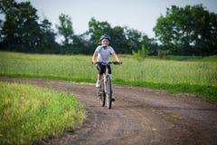 A menina de sorriso monta na bicicleta na paisagem rural Imagem de Stock
