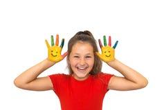 A menina de sorriso mostra as mãos pintadas com caras de sorriso imagem de stock