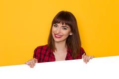 Menina de sorriso na bandeira vermelha de Shirt Behind White do lenhador Foto de Stock