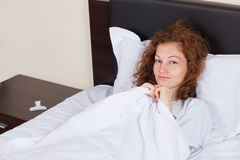 Menina de sorriso na cama Foto de Stock Royalty Free