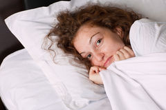Menina de sorriso na cama Imagem de Stock Royalty Free