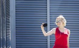 A menina de sorriso na camisa vermelha que toma uma foto no smartphone, contra o metal listrou o fundo Dia, exterior Fotografia de Stock Royalty Free