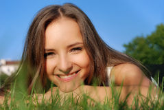 Menina de sorriso na grama Imagem de Stock Royalty Free