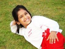 Menina de sorriso na grama Fotos de Stock Royalty Free