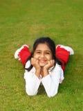 Menina de sorriso na grama Imagens de Stock Royalty Free