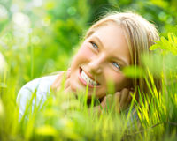 Menina de sorriso na grama verde Imagem de Stock Royalty Free