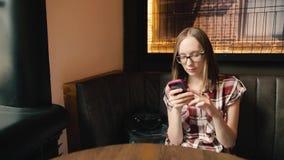 Menina de sorriso na moda nos vidros que conversa em redes sociais ou que lê algo filme