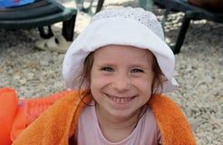 Menina de sorriso na toalha alaranjada foto de stock royalty free