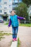 A menina de sorriso no campo de jogos está equilibrando na Imagens de Stock Royalty Free