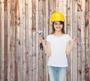 Menina de sorriso no capacete de segurança com martelo Fotografia de Stock Royalty Free