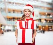 Menina de sorriso no chapéu do ajudante de Santa com presentes Foto de Stock