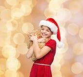 Menina de sorriso no chapéu do ajudante de Santa com urso de peluche Fotografia de Stock Royalty Free
