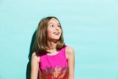 Menina de sorriso no fundo de turquesa que olha acima Fotografia de Stock Royalty Free