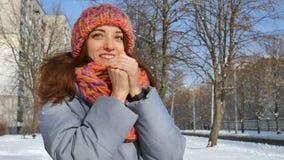 Menina de sorriso no revestimento morno e ar livre feito malha colorido do tempo da despesa do chapéu e do lenço durante o dia en filme