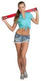 Menina de sorriso no short e camisa que guarda o vermelho Foto de Stock