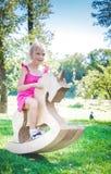 Menina de sorriso no unicórnio do brinquedo Piquenique no parque Fotografia de Stock