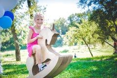 Menina de sorriso no unicórnio do brinquedo Piquenique no parque Imagens de Stock Royalty Free