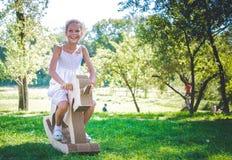 Menina de sorriso no unicórnio do brinquedo Raça misturada - africano e caucasian Piquenique no parque Imagens de Stock Royalty Free