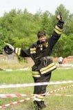 A menina de sorriso no uniforme do sapador-bombeiro com o capacete em sua mão exulta o curso de obstáculo após ele que passa vert imagem de stock royalty free