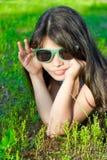 Menina de sorriso nos óculos de sol na grama verde Imagens de Stock Royalty Free