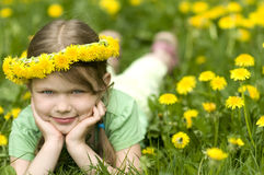 Menina de sorriso nos dentes-de-leão foto de stock