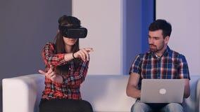 Menina de sorriso nos vidros da realidade virtual que descrevem algo a um homem que senta-se ao lado dela e que datilografa no po Imagens de Stock