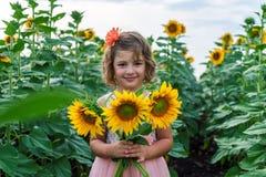 Menina de sorriso nova com girassóis Fotos de Stock Royalty Free