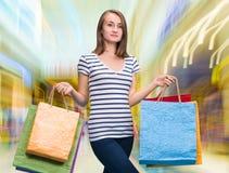 Menina de sorriso nova com sacos de compras Imagem de Stock