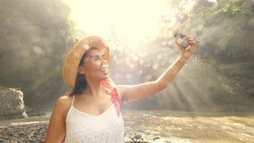 Menina de sorriso nova do turista da raça misturada no vestido e em Straw Hat Making Selfie Photos brancos que usa o telefone cel vídeos de arquivo