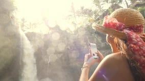 Menina de sorriso nova do turista em Straw Hat Making Photos de surpreender a cachoeira de Tegenungan usando o telefone esperto m filme