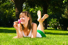 A menina de sorriso nova encontra-se na grama Imagem de Stock