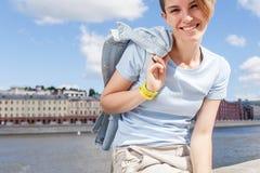 A menina de sorriso nova est? sentando-se na terraplenagem do rio na cidade fotografia de stock