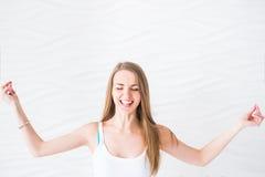 A menina de sorriso nova na camiseta interioa branca faz a meditação no exercício da ioga fotos de stock royalty free