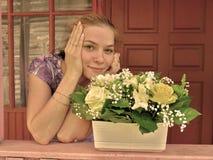 Menina de sorriso nova no patamar com um potenciômetro de flores brilhantes Imagens de Stock