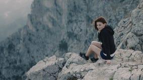 A menina de sorriso nova senta-se na borda da montanha vídeos de arquivo