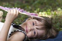 Menina de sorriso pequena bonito com os olhos azuis que encontram-se na grama Imagem de Stock