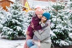 Menina de sorriso pequena bonito e mãe da criança no mercado da árvore de Natal Fotografia de Stock Royalty Free
