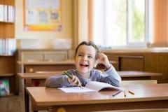 A menina de sorriso pequena caucasiano que senta-se na mesa na sala de classe e come?a a tirar com cuidado em um caderno puro Alu fotografia de stock royalty free