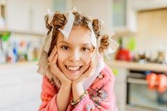 Menina de sorriso pequena com os encrespadores de cabelo em sua cabeça Imagens de Stock Royalty Free