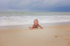 A menina de sorriso pequena encontra-se na praia em um dia nebuloso Imagens de Stock Royalty Free