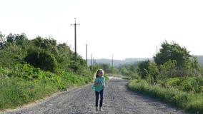 Menina de sorriso pequena que corre em uma estrada rural para a câmera Movimento lento video estoque
