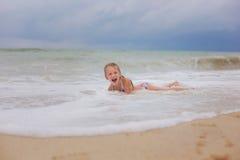 Menina de sorriso pequena que joga em ondas de oceano na praia Imagens de Stock Royalty Free