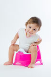 Menina de sorriso pequena que senta-se em um potenciômetro No fundo branco fotos de stock royalty free