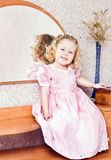 Menina de sorriso pequena que senta-se no espelho Fotografia de Stock